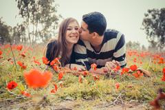 Man kissing woman and she has a toothy smile - stock photo