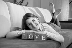 """Monochrome portrait of happy woman lying on couch with word """"love"""" Stock Photos"""