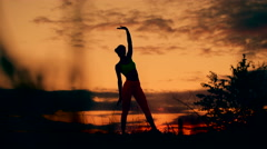 Slender young woman doing fitness exercises in the warm-up at sunset. Flexible Stock Footage