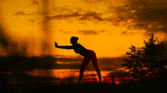 Silhouette of woman standing at yoga pose during an amazing sunset Stock Footage