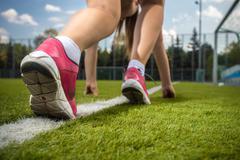 woman runner feet on start line on grass - stock photo