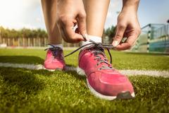 woman tying laces on sneakers on grass field - stock photo