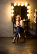 Blonde woman sitting on chair at dressing room with vintage mirror Stock Photos