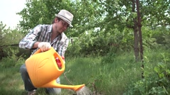 A young man in the garden watering the plants from a watering can Stock Footage