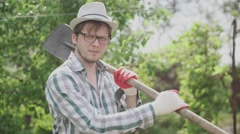 A young male farmer holding a shovel and smiling in the garden Stock Footage