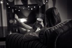 Monochrome photo of cute woman sitting at fireplace with cup of tea - stock photo