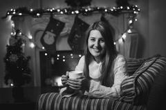 Monochrome portrait of smiling woman drinking tea at fireplace at Christmas - stock photo