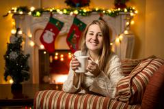 Woman sitting at fireplace with cup of tea at Christmas Stock Photos