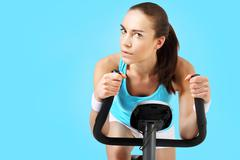 Exercise on a stationary bike, a woman in a fitness club - stock photo