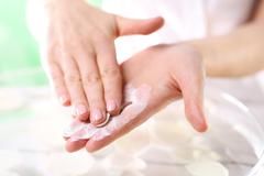 The woman imposes on hand scrub cosmetic Stock Photos