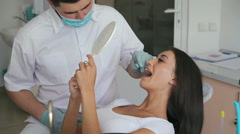 Woman having a check up at dentist's surgery with mirror Stock Footage