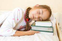 Photo of little girl sleeping in bed on pile of books Stock Photos