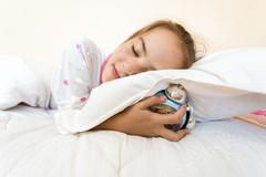 photo of little girl sleeping and holding alarm clock under pillow - stock photo