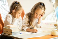 Older sister explaining homework to younger Stock Photos