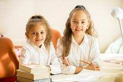 Two classmates sitting at desk and smiling - stock photo