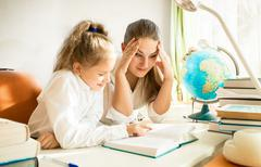 confused mother looking at daughters complicated homework - stock photo