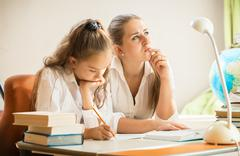 Mother trying to solve complicated exercise with little daughter Stock Photos