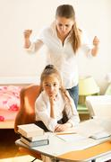 angry mother swears on daughter doing homework - stock photo