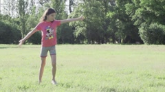 teen girl doing gymnastic wheel on a meadow Slow Motion - stock footage