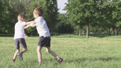 Children boy playing and fighting in the meadow Slow Motion - stock footage