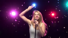 Blonde girl singing and dancing with retro microphone. Slow motion Stock Footage