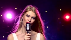 Singer girl with retro microphone, long hair developing. Slow motion Stock Footage