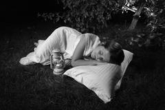 Monochrome photo of woman sleeping at garden at night Stock Photos