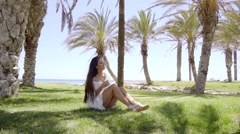 Smiling cute woman sitting on green grass Stock Footage