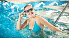 woman in bikini and goggles smiling at camera at swimming pool - stock photo