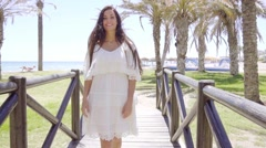 Pretty woman on little bridge at beach Stock Footage