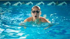 young swimmer woman taking a breath at swimming pool - stock photo