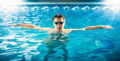 young male swimmer taking a breath and relaxing at pool - stock photo