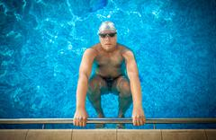 Male athlete holding on edge of swimming pool and preparing to swim Kuvituskuvat