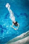 woman in long white dress diving underwater at swimming pool - stock photo