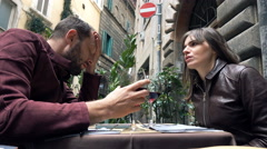Young couple fighting, arguing while sitting in cafe in city Stock Footage