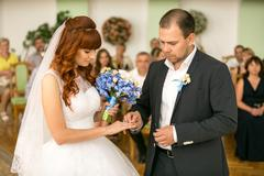 handsome groom putting wedding ring on brides hand at registry office - stock photo