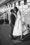 Monochrome shot of bride and groom kissing on pier against cruise ship - stock photo