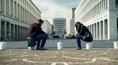 Offended couple sitting by street in city Stock Footage