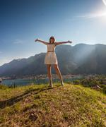 Woman standing on top of mountain and stretching out hands Stock Photos