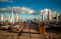 Rows of sunbeds and umbrellas at hotel at early morning Stock Photos