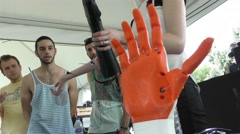 A woman demonstrates a robotic bionic hand to the help of amputated persons Stock Footage