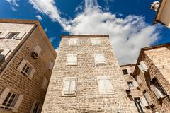 stone building with closed windows at sunny day - stock photo
