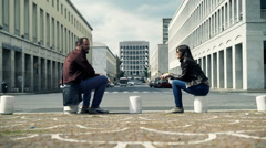 Young couple resting and talking sitting by street in city  Stock Footage