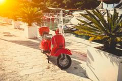 photo of vintage red scooter parked on street at sunny day - stock photo