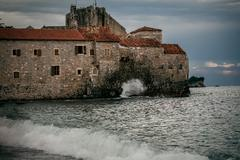 Stone citadel on high cliff at late evening in stormy sea Stock Photos