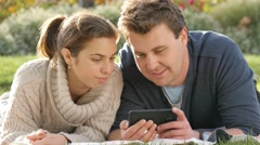 Couple in twenties looking and laughing at social media on smart phone device - stock footage