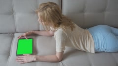 Beautiful girl using tablet pc with pre-keyed green screen laying on sofa - stock footage