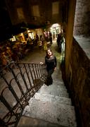 night shot of woman in dress walking up the stairway on street - stock photo