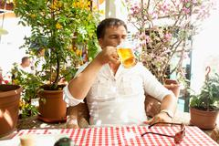 young man drinking beer at hot day on restaurant summer terrace - stock photo