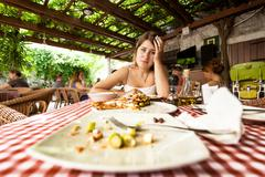 portrait of overeating woman looking at empty plates on table - stock photo